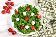 Vegetarisch voedsel en gezond levensstijlconcept - spring salade met kersentomaat, mozarellakaas en arugula op Stock Fotografie