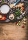 Vegetarische Aziatische keukeningrediënten met gehakte groenten, kokosmelk, zaden, kruiden en eetstokjes op rustieke houten backg stock fotografie