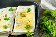 Vegetarische Burritosverpackungen mit Bohnen, Avocado und Käse auf einem Schiefer Lizenzfreies Stockfoto