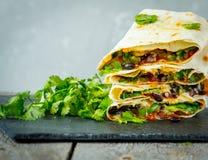Vegetarische Burritosverpackungen mit Bohnen, Avocado und Käse auf einem Schiefer Lizenzfreie Stockbilder