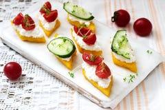 Vegetarische Canapes vom Polenta mit Käse, Gemüse und Kresse auf einem hellen Hintergrund Rustikale Art lizenzfreie stockfotografie