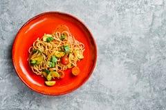 Vegetarische deegwaren met tomaten, avacado en pompoen Grijze achtergrond, hoogste mening, ruimte voor tekst stock foto's