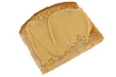 Vegetarische die Pindakaas op Volkorenmeel Geroosterd Brood wordt uitgespreid stock afbeeldingen