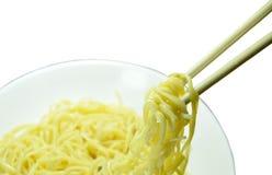 Vegetarische gelbe Nudeln, die in den Essstäbchen auf Platte auswählen stockfotos