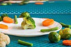 Vegetarische groenten: broccoli, Spruitjes, bloemkool, wortelen en slabonen op een wit plaat en een blauw Stock Fotografie