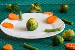 Vegetarische groenten: broccoli, Spruitjes, wortelen en slabonen op een witte plaat en een groene achtergrond Royalty-vrije Stock Afbeeldingen