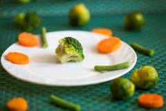 Vegetarische groenten: broccoli, Spruitjes, wortelen en slabonen op een witte plaat en een groene achtergrond Stock Afbeeldingen