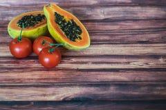 Vegetarische ingrediënten op houten textuurachtergrond Hoogste mening van papaja, tomaat Stock Foto