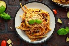 Vegetarische Italiaanse alla Norma van de Deegwarenspaghetti met aubergine, tomaten, basilicum en parmezaanse kaaskaas stock afbeeldingen