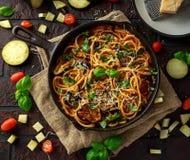 Vegetarische Italiaanse alla Norma van de Deegwarenspaghetti met aubergine, tomaten, basilicum en parmezaanse kaaskaas in rustiek stock foto's