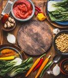 Vegetarische kokende ingrediënten met kekersschotel, kleurrijke kruiden, tomatendeeg, gember en groenten rond houten knipsel royalty-vrije stock afbeelding