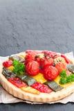 Vegetarische quiche met gekleurde peper en kersentomaten op bl royalty-vrije stock afbeeldingen