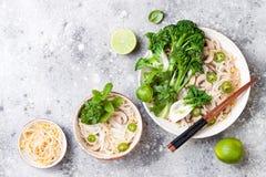 Vegetarische traditionele Vietnamese soep Pho BO met kruiden, rijstnoedels, broccolini, bok choy Aziatisch voedselconcept stock foto's