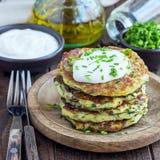 Vegetarische Zucchinistückchen oder -pfannkuchen, gedient mit griechischem Jogurt und Frühlingszwiebel auf hölzerner Platte, Quad stockbilder
