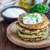 Vegetarische Zucchinistückchen oder -pfannkuchen, gedient mit griechischem Jogurt und Frühlingszwiebel auf hölzerner Platte, quad lizenzfreie stockfotografie