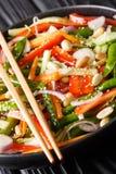 Vegetarischer Gemüsesalat mit indischem Sesam und Erdnussnahaufnahme auf einer Platte vertikal stockfoto