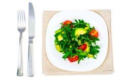 Vegetarischer Salat des Vitamins vom Arugula und von der Avocado auf weißer Platte Stockfotografie
