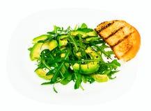 Vegetarischer Salat des Vitamins vom Arugula und von der Avocado auf weißer Platte Stockbilder