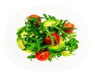 Vegetarischer Salat des Vitamins vom Arugula und von der Avocado auf weißer Platte Lizenzfreies Stockfoto