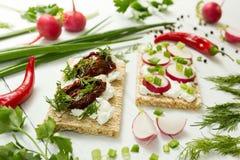 Vegetarisches Mittagessen des rohen Gemüses mit Ricottakäse, sonnengetrockneten Tomaten, Kräutern und Rettich auf einem weißen Ho stockfoto