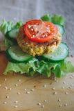 Vegetarisches Sandwich mit Kichererbsenlinsenkotelett, Gurke, frischem Kopfsalat und Tomate Besprühen Sie mit Samen des indischen Stockfoto
