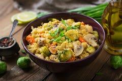 Vegetarisk couscoussallad med brussels groddar, champinjoner, morötter och kryddor Royaltyfri Foto