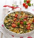 Vegetarisk eldfast form med pasta, zucchinin, körsbärsröda tomater, sparris och lökar arkivbilder