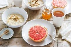 Vegetarisk frukost för två av havremjöl, bakad grapefrukt och te Lantlig stil royaltyfri bild