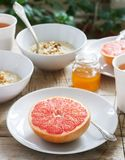 Vegetarisk frukost för två av havremjöl, bakad grapefrukt och te Lantlig stil arkivfoton