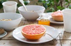 Vegetarisk frukost för två av havremjöl, bakad grapefrukt och te Lantlig stil royaltyfri foto