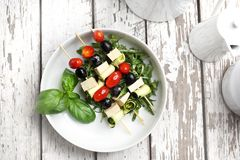 Vegetarisk gr?nsakshashlik gjorde av k?rsb?rsr?da tomater, mozzarellaen och svarta oliv royaltyfri fotografi