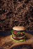 Vegetarisk hamburgare med falafellilla pastejen på det lantliga träbrädet, bakgrund för hösugrörtextur Royaltyfria Bilder