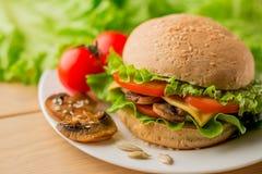 Vegetarisk hamburgare med ny sallad på plattan, slut upp arkivfoton