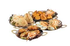Vegetarisk indisk mat eller startknappar på metallplattor inklusive samosa på vit bakgrund Arkivfoto