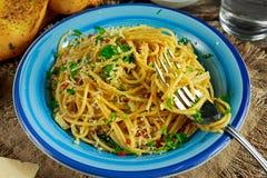 Vegetarisk italiensk pastaspagettiAglio E Olio med vitlökbröd, den röda chiliflingan, persilja, parmesanost och glas av Arkivfoton