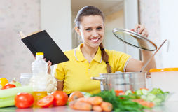 Vegetarisk mat för kvinnamatlagning med kokboken Royaltyfria Bilder