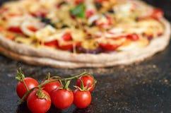 Vegetarisk pizza med tomater, spansk peppar, lök, svarta oliv, ost, kryddor på den svarta bakplåten på suddig svart bakgrund Arkivfoto
