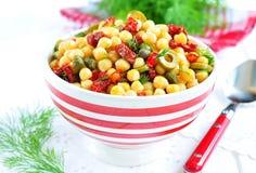 Vegetarisk sallad med kikärtar, torkade tomater, kapris och dill Arkivbild