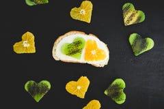 Vegetarisk smörgås med sockerkräm, citrus med kiwi på den svarta tabellen Lekmanna- lägenhet, bästa sikt royaltyfri fotografi