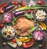 Vegetariska matlagningingredienser för sund matlagning och att äta Olika grönsakingredienser runt om träplattan med att laga mat  Arkivfoton