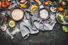 Vegetariska matlagningingredienser med citronen, ris och grönsaker på mörk lantlig bakgrund, bästa sikt, gräns Sunt eller banta m royaltyfri bild