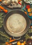 Vegetariska matlagningingredienser runt om mellanrumet åldras matlagning lägger in på det mörka lantliga köksbordet, bästa sikt Royaltyfri Foto