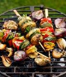 Vegetariska steknålar, grillade grönsaksteknålar av zucchinin, peppar och potatisar med tillägget av aromatiska örter och olivolj arkivfoto