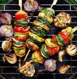 Vegetariska steknålar, grillade grönsaksteknålar av zucchinin, peppar och potatisar med tillägget av aromatiska örter och olivolj arkivbild