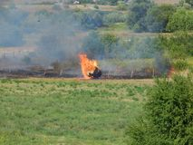 Haystack in fire in a hot summer day. Vegetation fire emitting smoke Royalty Free Stock Image