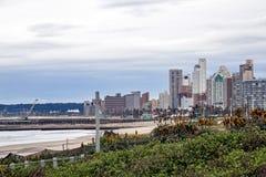 Vegetazione ed aloe delle dune contro l'orizzonte nuvoloso della città Fotografia Stock Libera da Diritti