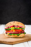 Veggie beet burger on a white wooden table and black background. Veggie beet burger with lamb's lettuce, tomato, radish and cucumber on a white wooden table and Royalty Free Stock Photo