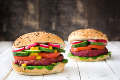 Veggie beet burgers on a white wooden table. Two Veggie beet burgers on a white wooden table Stock Image