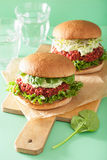 Veggie beet and quinoa burger with avocado dressing Stock Photo