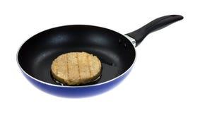 Veggie burger cooking in skillet Stock Images